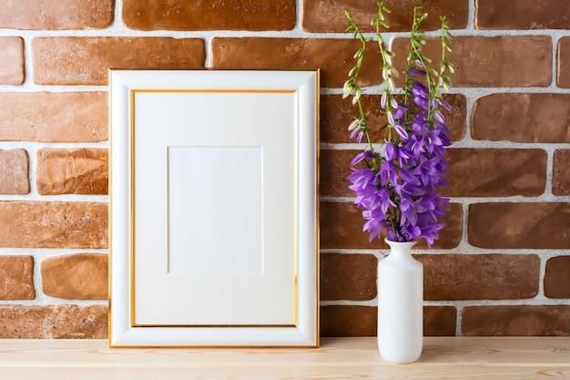 Gold verzierte rahmenmodell mit herausgestellter backsteinmauer des glockenblumenblumenstraußes