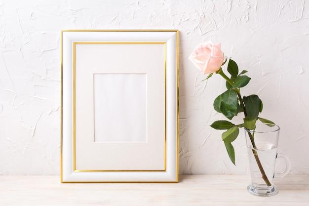 Gold verziertes rahmenmodell mit zarter rosarose im glas