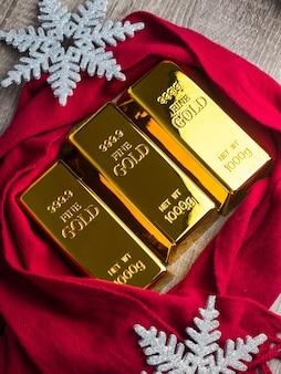 Goldbarren als weihnachtsgeschenk auf holztisch mit ornamenten.