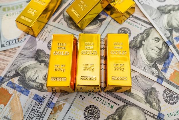 Goldbarren auf amerikanischen dollarnoten. finanzielles sparkonzept