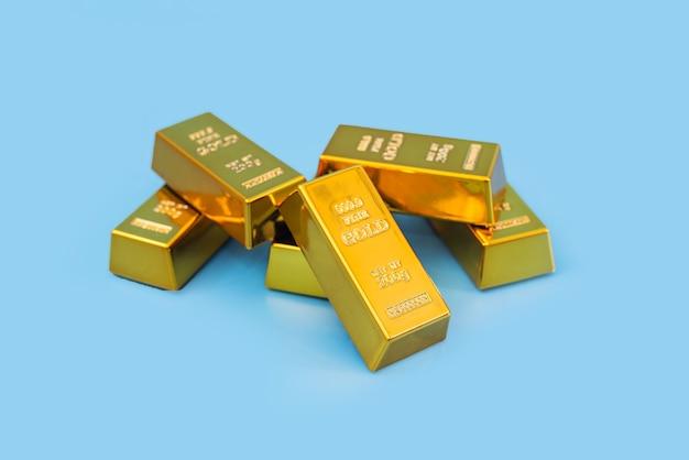 Goldbarren auf einem blauen tisch. finanzkonzept.