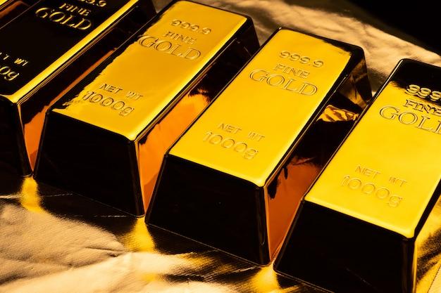Goldbarren auf glänzendem gelbem hintergrund.