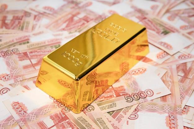 Goldbarren auf russischem geldhintergrund mit 5000 rubel-banknoten
