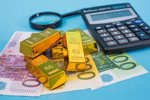 Goldbarren, euro-banknoten, taschenrechner und lupe auf einem blauen tisch.