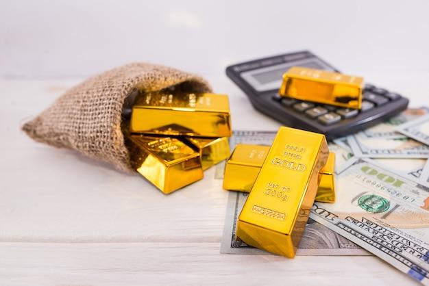 Goldbarren und taschenrechner mit dollar. vermögenskonzept.