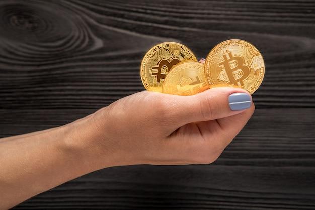 Goldbitcoin in den händen an der frau vor dem hintergrund eines holztischs