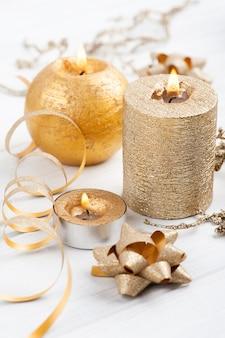 Golden beleuchtete aromakerzen und weihnachtsspielzeug auf rustikalem holz