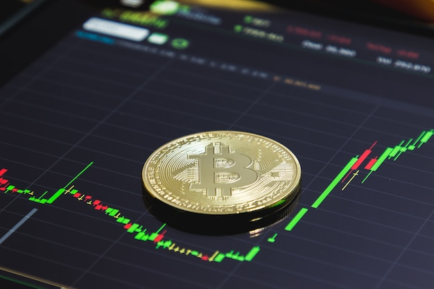 Golden bitcoin und kursdiagramm auf tablets.