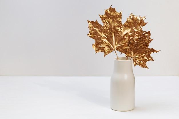 Golden gemalte ahornblätter in der keramikvase auf weißem tisch