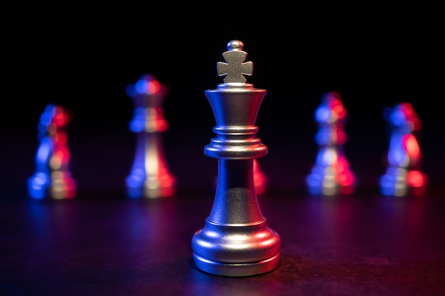 Golden king chess stehend im vordergrund auf schwarzem hintergrund mit roten und blauen lichtern