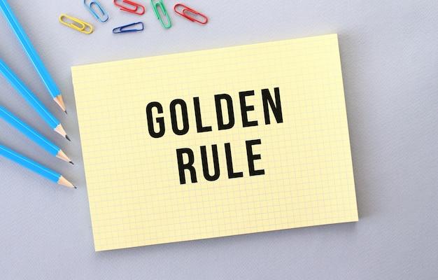 Golden rule text im notizbuch auf grauem hintergrund neben stiften und büroklammern. konzept.