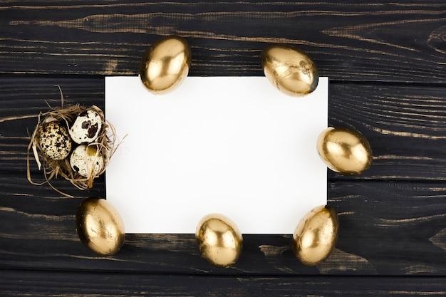 Golden und wachteleier um papierblatt