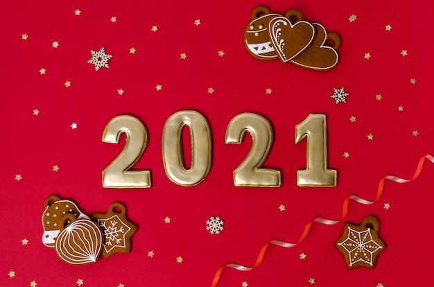 Goldene 2021-zahlen liegen auf einer roten fläche mit keksen und sternen