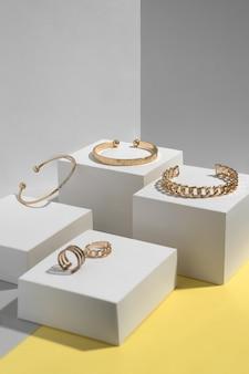 Goldene accessoires auf weißen würfeln auf gelben und grauen geometrischen
