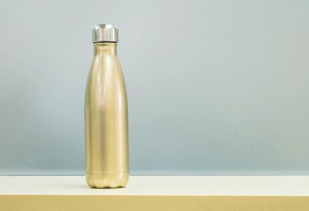 Goldene aluminiumflasche für warmwasser auf unscharfen schreibtisch aus holz