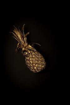 Goldene ananas auf schwarzem hintergrund, stilvolle minimalistische komposition mit exemplar für werbung. modische trendige farbkombination. essen, obst, süßigkeiten, sommerstimmungskonzept. plakat, tapete.