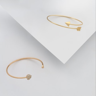 Goldene armbänder der herzform und der pfeilform auf weißem papierhintergrund
