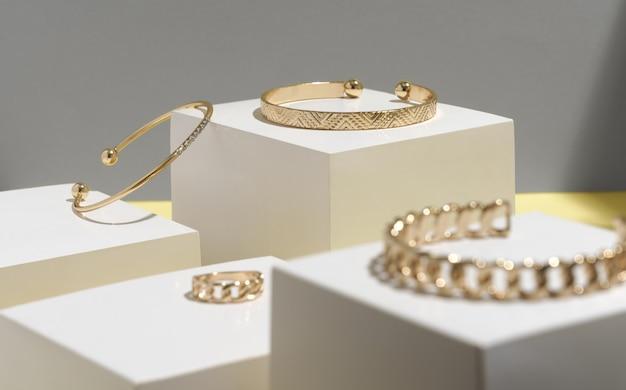 Goldene armbänder und ring auf weißen kubischen blöcken mit kopierraum