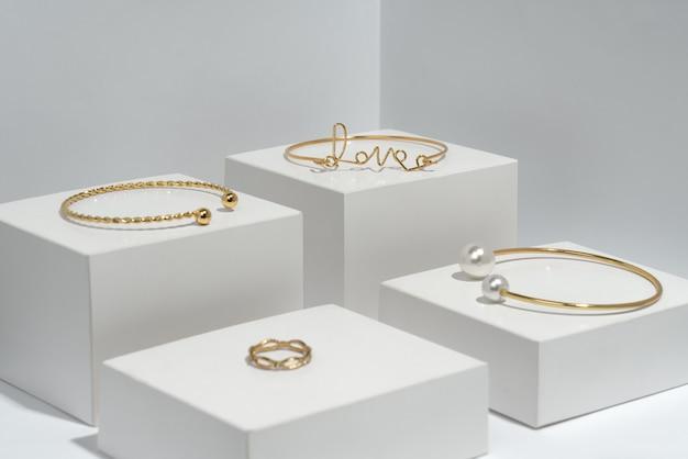 Goldene armbänder und ring auf weißen würfeln mit kopierraum