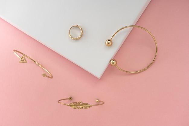 Goldene armbänder und ring des modernen designs auf rosa und weißem hintergrund