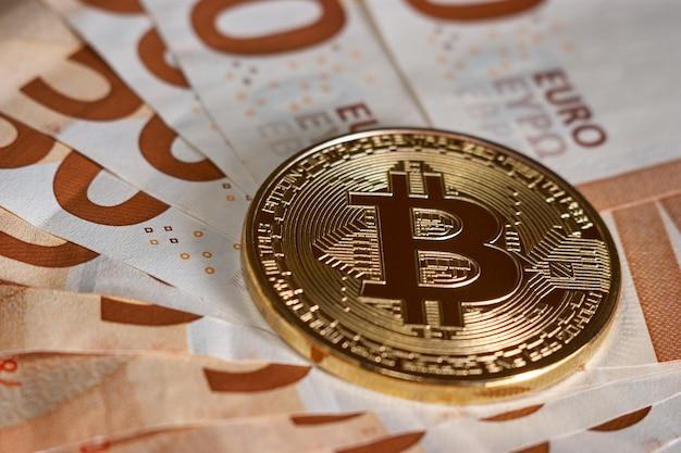 Goldene bitcoin auf fünfzig euro banknoten hintergrund. bitcoin-kryptowährung, blockchain-technologie, digitales geld