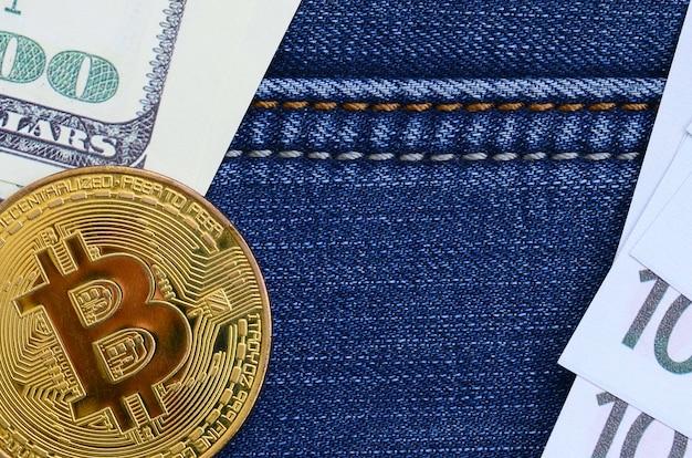 Goldene bitcoin-, dollar- und eurorechnungen liegen auf einem jeansstoff