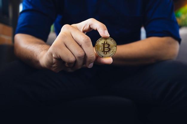 Goldene bitcoin in einer geschäftsmannhand im büro