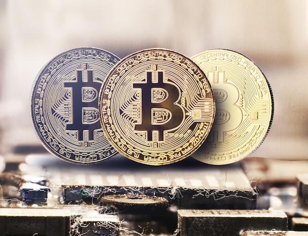 Goldene bitcoin-kryptowährung auf einer computerchipplatine, elektronische währung, internetfinanzierung, mikroschuss im gelben hintergrund.