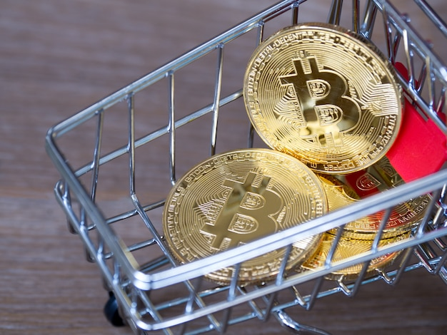 Goldene bitcoin kryptowährung im roten warenkorb auf schreibtischholz.