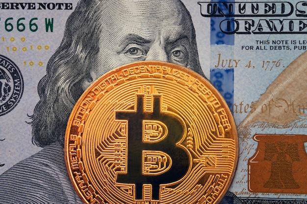 Goldene bitcoin mit bösem, bösem benjamin franklin-porträt von hundert amerikanischen dollar. geschäftskonzept der weltweiten kryptowährung. einnahmen aus dem mining von kryptowährungen.