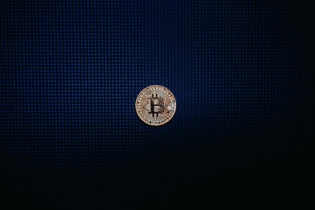 Goldene bitcoin münze getrennt auf blauer dunkelheit