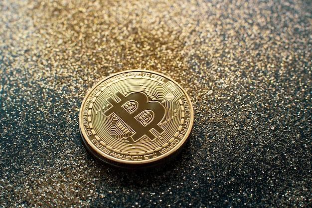 Goldene bitcoin-münze mit funkeln beleuchtet schmutzkrypto währungshintergrundkonzept