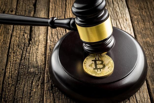 Goldene bitcoin münze mit richter wood hammer law judges-hintergrundkonzept