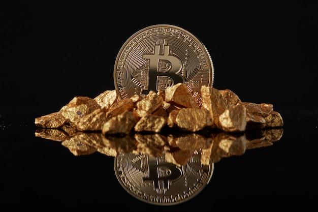 Goldene bitcoin-münze und goldhügel mit reflexion. konzept zur finanzierung der bitcoin-kryptowährung in edelmetall
