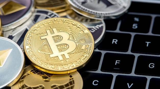 Goldene bitcoin-währung des physischen metalls auf notebook-computertastatur. weltweites virtuelles internetgeld. digitaler münz-cyberspace, kryptowährung gold btc. investition online-zahlung