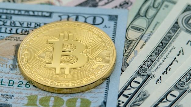 Goldene bitcoin-währung des physischen metalls über dollarnoten der vereinigten staaten. weltweites virtuelles internetgeld mit usa-banknoten. digitaler münz-cyberspace, kryptowährung gold btc. onlinebezahlung