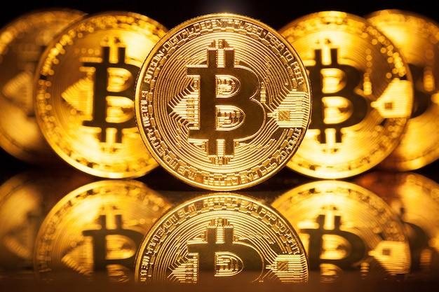 Goldene bitcoins auf dunkler oberfläche