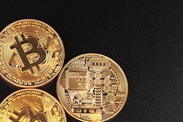 Goldene bitcoins auf schwarzem hintergrund. handelskonzept der kryptowährung