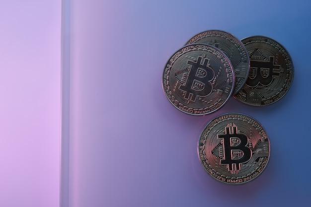 Goldene bitcoins einzeln auf neonblau-rosa-violettem hintergrund, nahaufnahme mit kopierraum, konzept des wachstums und fall der kryptowährung