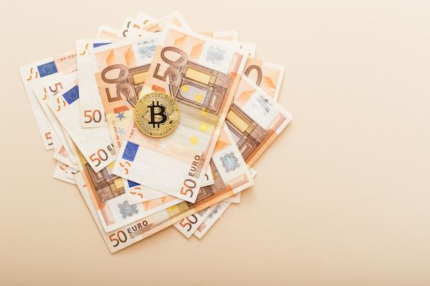 Goldene bitcoins mit euro-banknoten als hintergrund. virtuelle kryptowährung, digitales konzept.