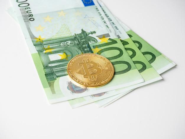Goldene bitcoins sind auf den scheinen von hundert euro. weißer hintergrund. seitenansicht. kryptowährungskonzept