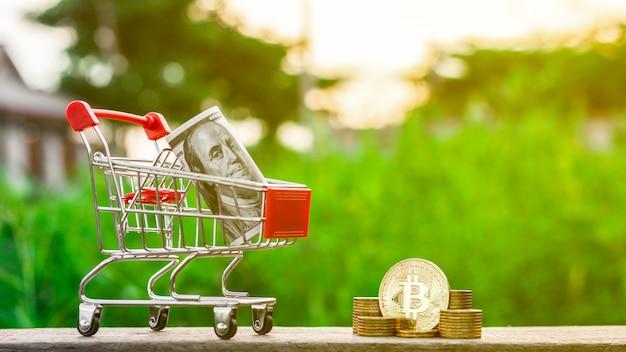 Goldene bitcoins und ein einkaufswagen in goldene münzen stapeln auf dem tisch.