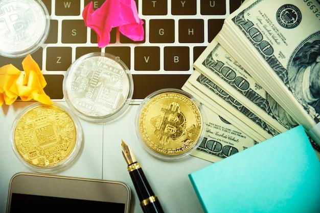 Goldene bitcoins und geld auf dem laptop. kryptowährung und mining-konzept.