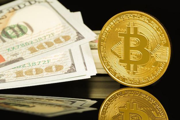 Goldene bitcoins und us-banknoten von einhundert dollar. nahaufnahme von metallglänzenden bitcoin-kryptowährungsmünzen und us-dollar