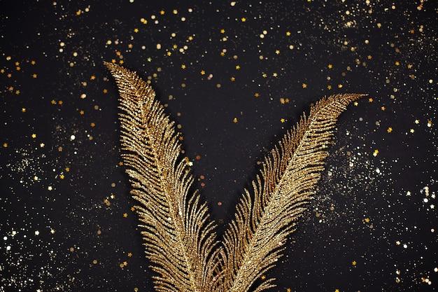 Goldene blätter auf schwarzem hintergrund. dekoration. festliches konzept.