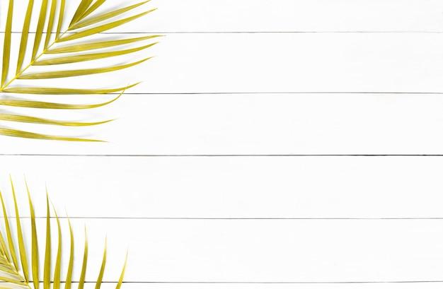 Goldene blätter der palme auf weißem holztischhintergrund, tropische goldene palmblätter, minimales konzept der draufsicht. flach liegen.