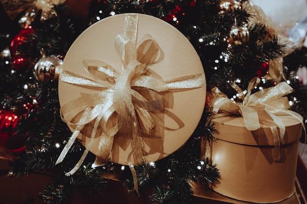 Goldene boxen geschenke mit bändern auf einem weihnachtsbaum weihnachtsfeier dekoration oder postkartenkonzept