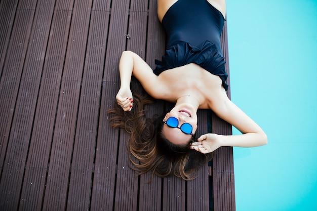 Goldene bräune bekommen. volle länge draufsicht der schönen jungen frau in der badebekleidung, die gesicht mit hut bedeckt, während sie sich am pool sonnen