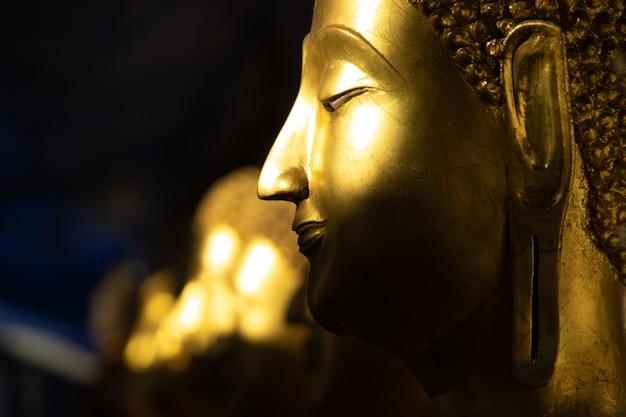 Goldene buddha-statue im licht und schatten der sonne am wat pra sri mahathat tempel.