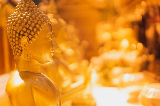 Goldene buddha-statue mit unscharfer goldener pagode